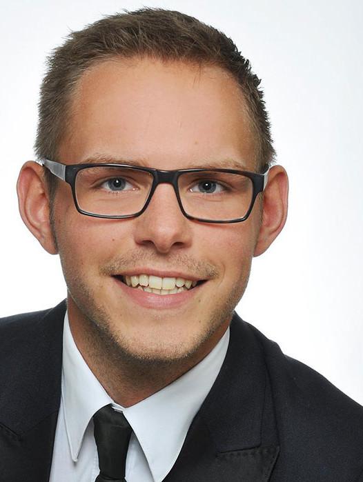 Portraitfoto zeigt jungen, freundlichen Mann mit Brille, Schlips und Anzug