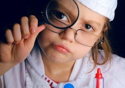 Ein Mädchen als Arzt verkleidet mit einer Spielzeugspritze, Kittel, Brille und einer Lupe, die sie sich vor das rechte Auge hält. Sie trägt einen Hut mit einem roten Kreuz drauf.