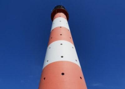 Ein rot-weiss gestreifter Leuchtturm von unten fotografiert mit blauem Himmel als Hintergrund.