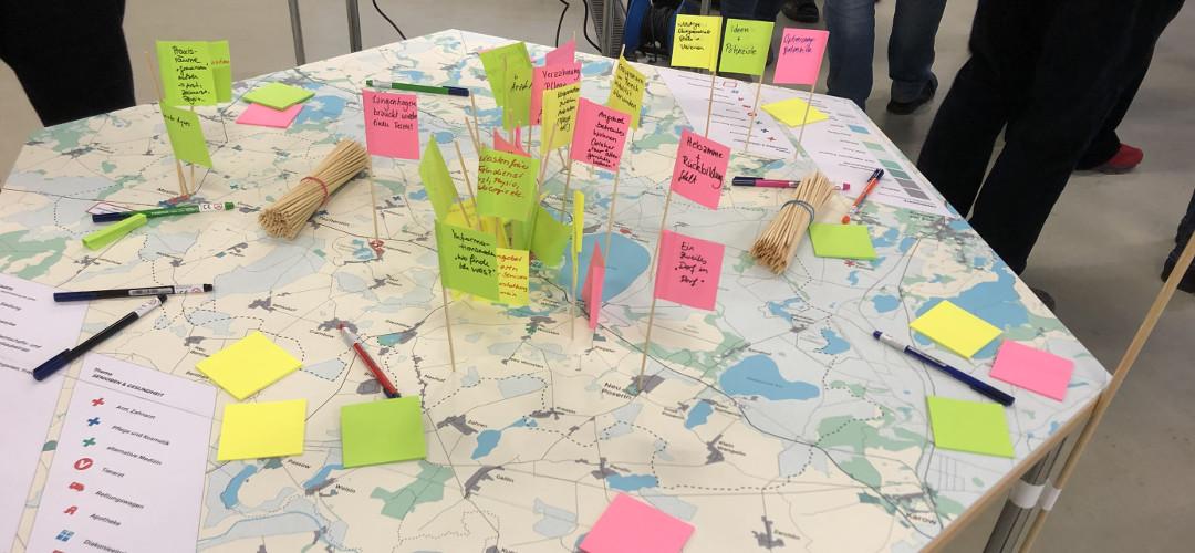 Tisch, auf dem eine Landkarte liegt, in die viele beschriftete Fähnchen gesteckt wurden.