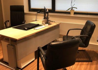 Ein Bürostuhl vor einem Schreibtisch mit Computer, auf der anderen Seite zwei weitere Stühle