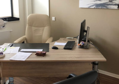Ein Schreibtisch mit Computer und Zetteln drauf