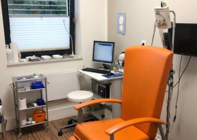 Orangener Untersuchungsstuhl sowie Verbandsmaterial und Computer im Hintergrund
