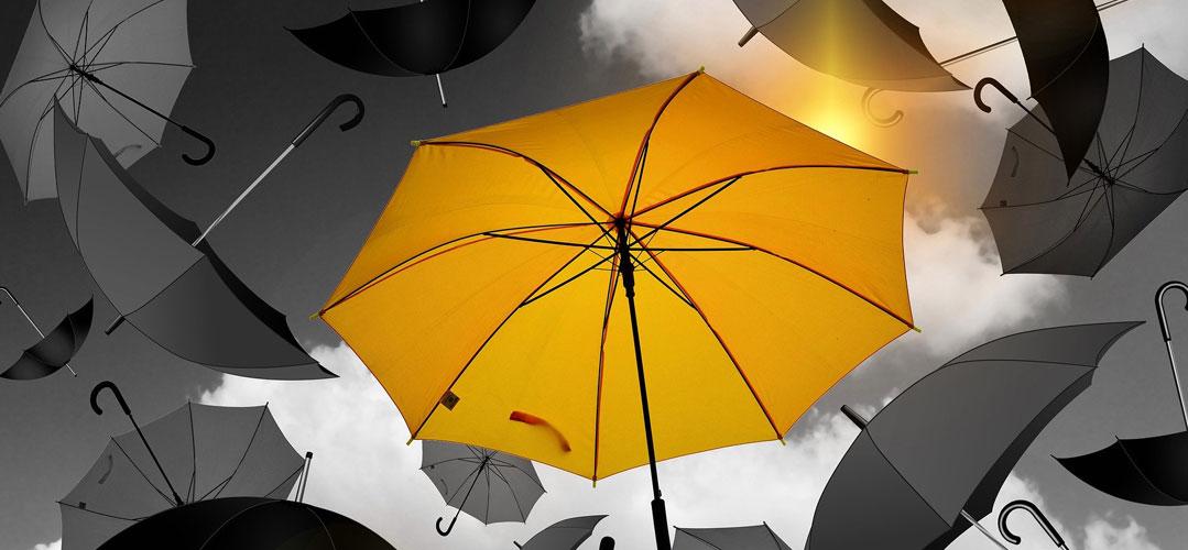 Fallende Regenschirme vor grauem Himmel. Ein Regenschirm ist gelb und groß in der Mitte.