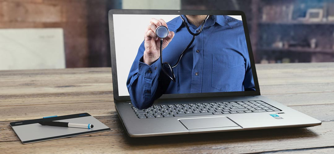 Ein Arzt ist auf dem Bildschirm eines Laptops zu sehen. Der Arzt hält ein Stethoskop hoch.