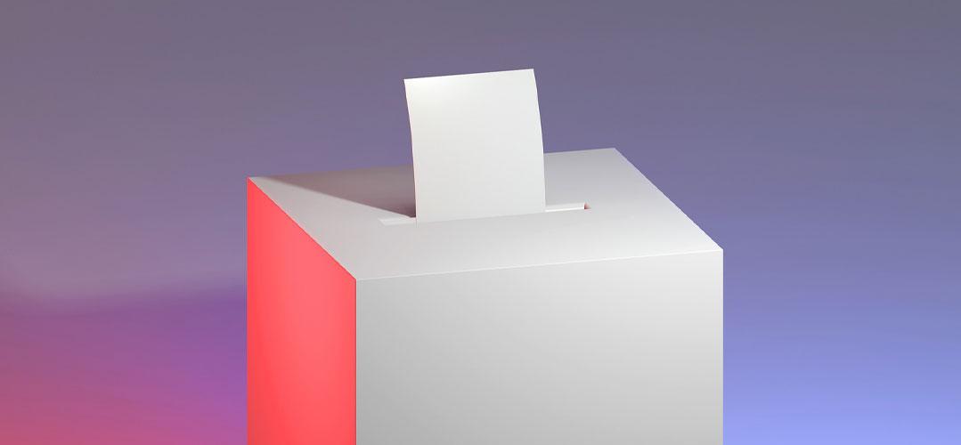 Stimmzettel steckt in einer Wahlurne