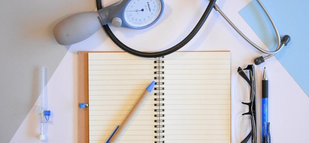Schreibblock mit Stift. Daneben Brille und Stethoskop