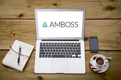 Schreibtisch mit Laptop und AMBOSS Logo auf dem Bildschirm