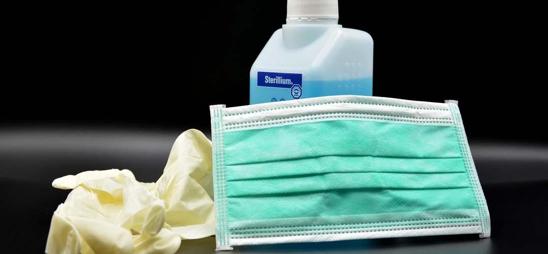Desinfektionsmittel, Handschuhe und eine Maske